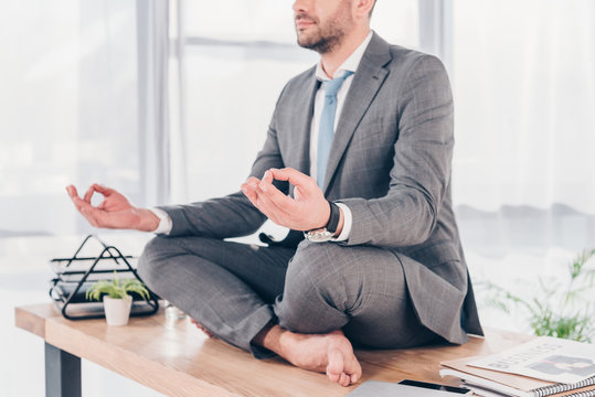 cropped view of businessman meditating in Lotus Pose on office desk
