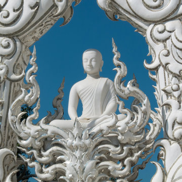 White temple, Wat Rong Khun in Chiang Rai, Thailand. White Buddha on a blue sky with his hands in the posture of meditation, serenity and calming . He closes his eyes to lifts his spirits.