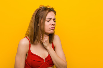 Young caucasian woman wearing bikini and sunglasses suffers pain in her throat due a virus or infection. Wall mural
