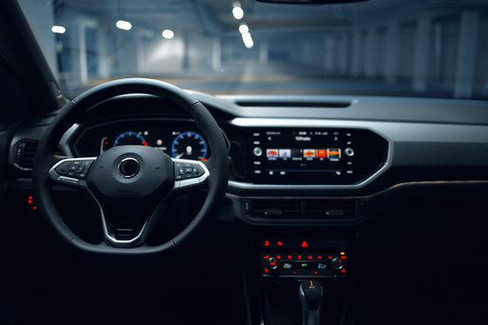 Modern car interior with multimedia and dashboard at underground parking