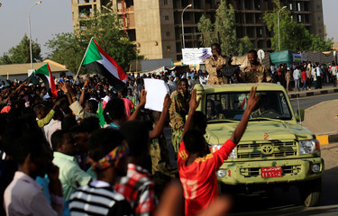 Protesters make victory signs and wave national flags as Sudanese soldiers are seen on an army vehicle in front of the defense ministry compound in Khartoum