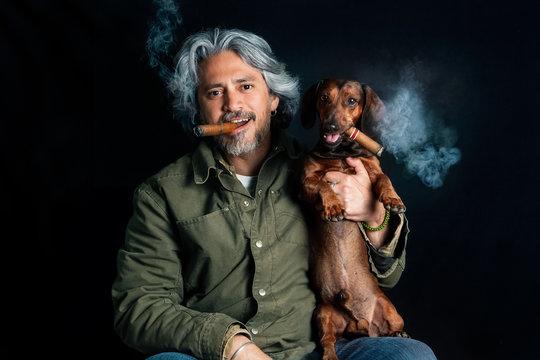 Studio portrait of man with dachshund smoking cigars