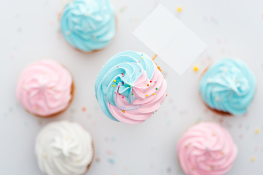 top view of delicious pink, white and blue cupcakes with sprinkles and blank card Isolated On White