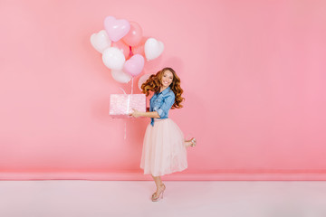 Full-length portrait of adorable laughing birthday girl, jumping with present box and balloons. Gorgeous young woman with curly hair having fun on party holding gift, isolated on pink background.
