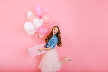 Excited long-haired girl in lush midi skirt standing on one leg, holding cute birthday present. Charming curly young woman in stylish outfit going to friend's party with gift and colorful balloons