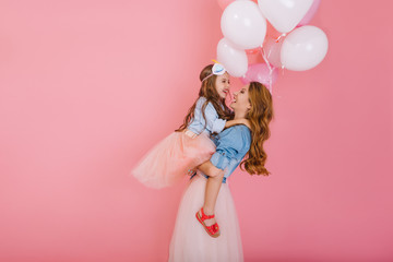 Portrait of happy little birthday girl with long hair holding balloons and hugging her young stylish mom after event. Charming excited mother posing with daughter at party isolated on pink background