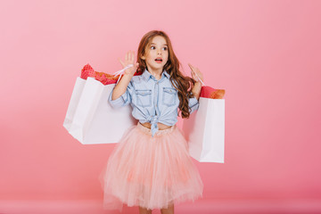 Amazing little astonished  girl in tulle skirt expressing to side with white packages in hands isolated on pink background. Young shopper with presents, shopping in childhood