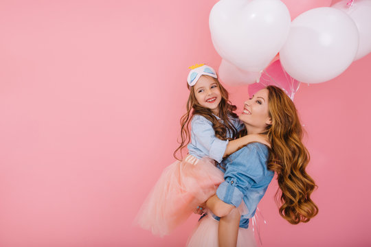 Adorable laughing birthday girl with colorful balloons embracing her young smiling mom after funny event. Attractive mother posing with pretty daughter in mask at party isolated on pink background