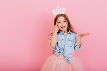 Joyful little girl with long brunette hair in tulle skirt holding princess crown on head isolated on pink background. Celebrating brightful carnival for kids, expressing positivity of birthday party