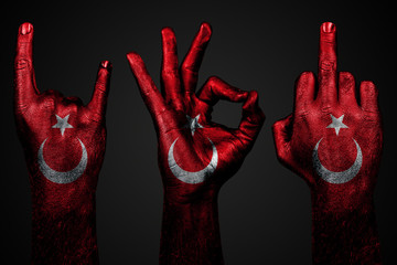 a set of three hands with a painted flag Turkey show middle finger, goat and Okay, a sign of aggression, protest and approval on a dark background. Fotoväggar