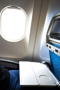 Airplane tray table opened on seat back by the window