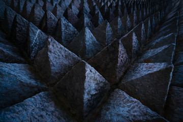Sharp tip concrete architecture texture background. Art picture of unique pattern of dark stone carving in pointed triangle shape. Concept of obstacle in work or living. Rough texture of concrete wall