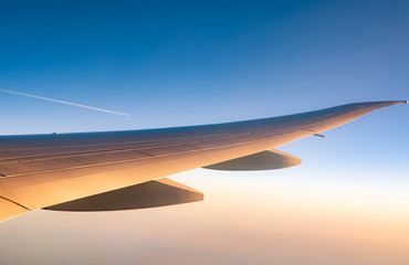 Wing of plane over the city. Airplane flying on blue sky. Scenic view from airplane window. Commercial airline flight in the morning with sunlight. Plane wing above clouds. Flight mechanics concept. Fototapete
