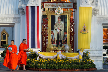 Buddhist monks walk outside Wat Benchamabophit or Marble Temple to collect alms next to a portrait of King Maha Vajiralongkorn a day before King's coronation in Bangkok
