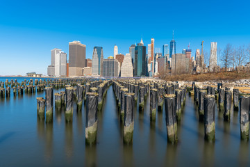 Fototapete - Scene of New york Cityscape river side with east river at the morning time under blue sky, USA downtown skyline, Architecture and building with tourist concept