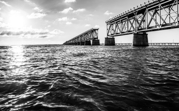 Black And White Ocean Level View Of The Rail Bridge In Bahia Honda State Park With The Bright Glow Of The Evening SunSet.