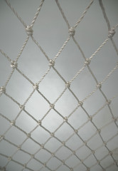 White Plastic Nylon Net From Rope on White Background. Polypropylene Twisted Rope Net. Selective Focus.