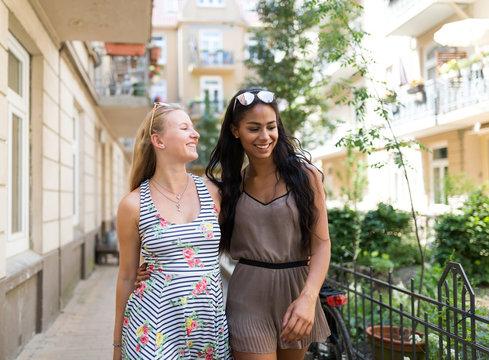Zwei Freundinnen flanieren auf dem Innenhof