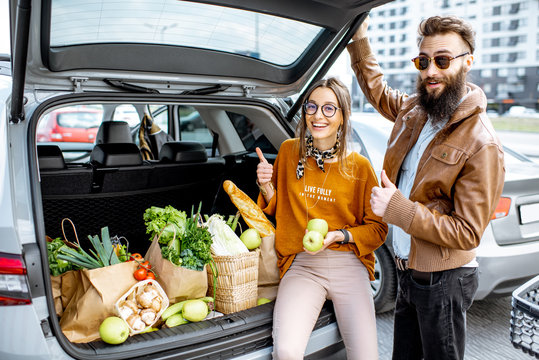 Young stylish couple having fun while sitting on the car trunk full of fresh and healthy food on the supermarket parking outdoors