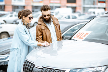 Young stylish couple choosing luxury car to buy on the open ground of the dealership Wall mural