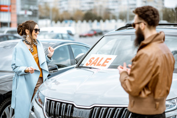 Young stylish couple choosing luxury car to buy on the open ground of the dealership