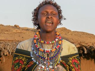close up of a maasai woman in green singing