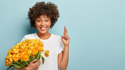 Indoor shot of smiling African American woman crosses fingers, believes in good luck, wears casual t shirt, holds big bouquet of orange spring flowers, stands over blue background with free space