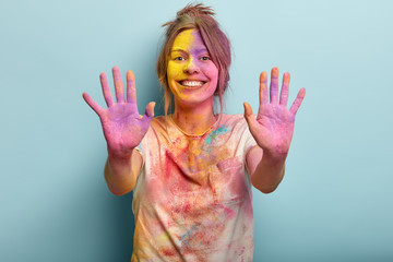 Fesitaval of Holy, fun concept. Pretty cheerful European young woman covered with colored paints, keeps dirty palms outstretched in camera, has glad expression, isolated over blue background.