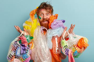 Photo of surprised red haired man has thick beard, overloaded with much garbage, collects plastic, looks with frustrated expression, raises hands, isolated oer blue background. Ecology concept