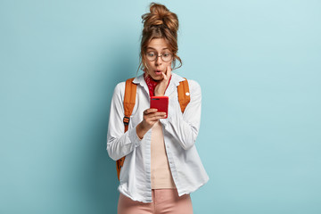 Image of astonished young female addicted to internet, networks via cell phone, surprised to have limits, has dark combed hair, focused at screen, carries backpack, isolated on blue background.