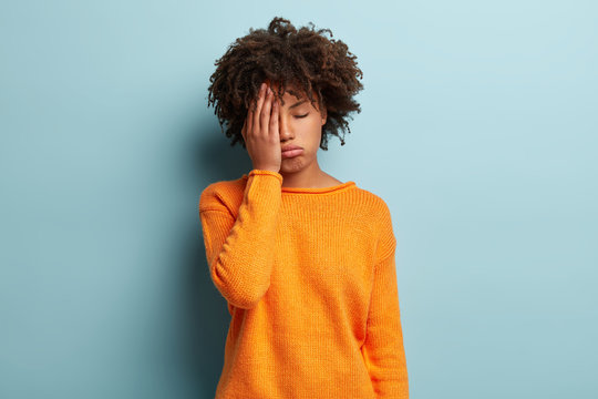 Photo of tired dark skinned female covers face, closes eyes, feels fatigue, needs good rest, dressed in orange jumper, has sleepy expression, isolated over blue background. Weariness and people