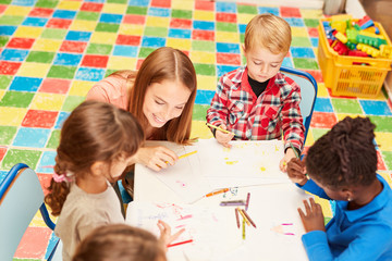 Erzieherin und Kinder zusammen im Zeichenkurs