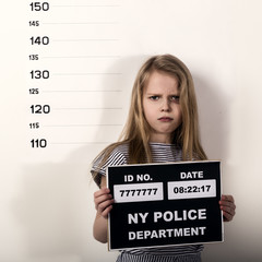 Young beautiful blonde child with a sign covers his face with his hand, Criminal Mug Shots