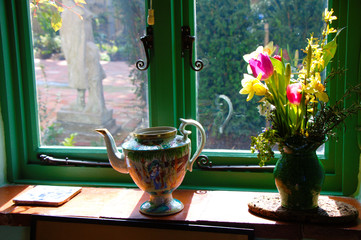Decorated window sill with flowers in a vase and a tea jug.