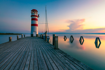 Lighthouse at Lake Neusiedl, Podersdorf am See, Burgenland, Austria. Lighthouse at sunset in Austria. Wooden pier with lighthouse in Podersdorf on lake Neusiedl in Austria. Wall mural