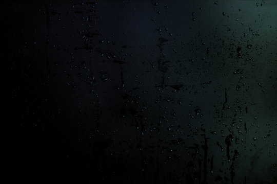 drops and splashes of water on a black matte background, texture for the designer