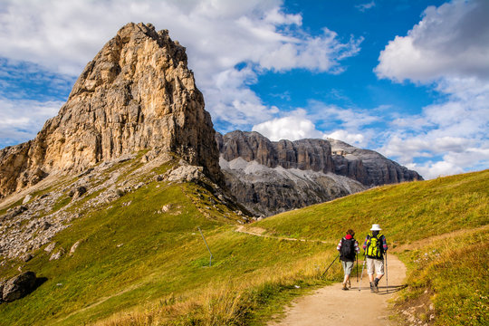 Active senior caucasian couple hiking in mountains with backpacks, enjoying their adventure. Location: Dolomites Alps, South Tyrol, Italy, Europe.