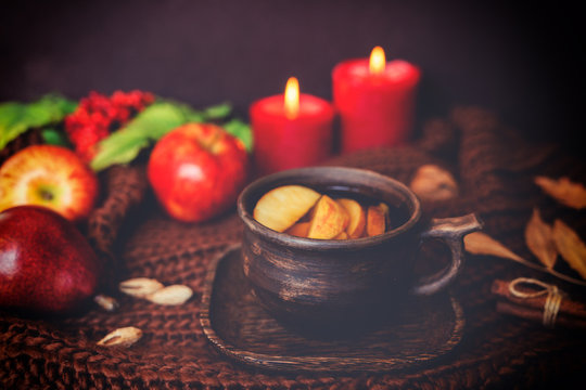 Fall leaves, hot cup of tea, knitted blanket, red berries, candles on wooden table background. Seasonal, autumnal hot drink. Autumn relaxing and still life concept. Toned image. Selective focus.