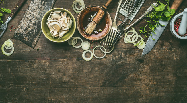 Kitchen utensils on rustic wooden background with fresh seasoning, BBQ simple marinade, top view. Copy space.