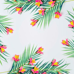 Wall Mural - Tropical background with palm leaves and exotic flowers on white background, top view. Frame. Flat lay. Copy space for your design