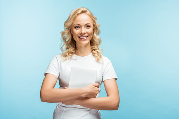 happy blonde woman looking at camera while holding digital tablet on blue