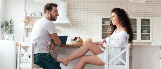 panoramic shot of sexy girl flirting with boyfriend in kitchen