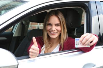 Junge Frau zeigt ihren Führerschein nach bestandener Fahrprüfung