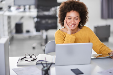 Beautiful smiling mixed race businesswoman dressed casual sitting in office and using laptop.