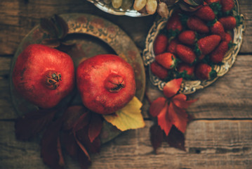 Fresh pomegranates, grapes and berries in an old vintage plate with leaves. On rustic wooden background. Free space for text . Top view. Toned image.