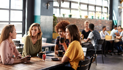 Four Young Female Friends Meeting Sit At Table In Coffee Shop And Talk Wall mural