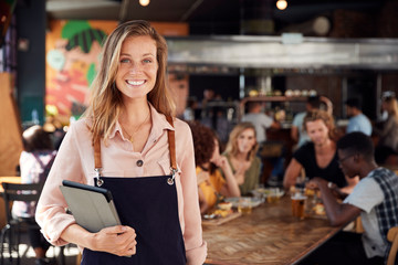 Foto op Canvas Restaurant Portrait Of Waitress Holding Menus Serving In Busy Bar Restaurant