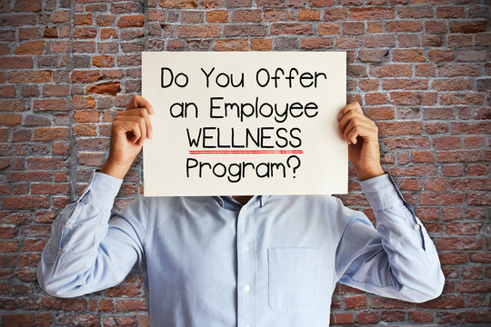 """Employee benefits concept with young businessman asking """"do you offer an employee wellness program?"""""""