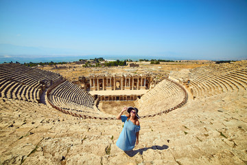 Woman traveler in hat looking at amazing Amphitheater ruins in ancient Hierapolis, Pamukkale, Turkey. Grand panoramic view Fototapete
