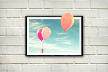 Frame with air balloons on a white brick wall, thinking outside the box concept